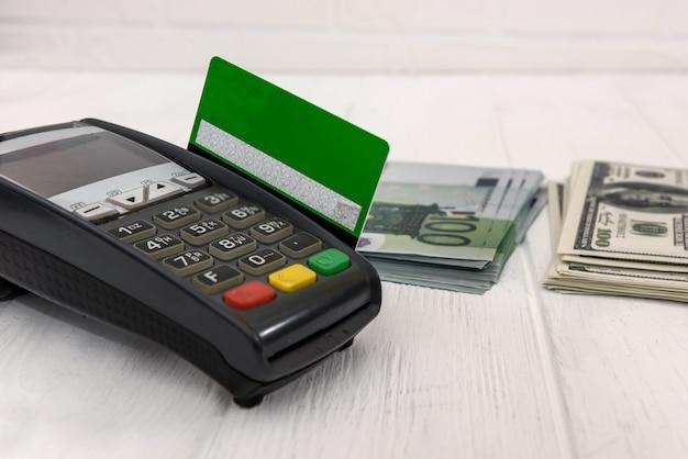 Terminale bancario con una pila di banconote in euro e dollari