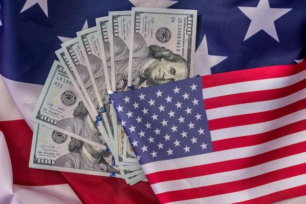 Banconote del dollaro americano sulla bandiera nazionale