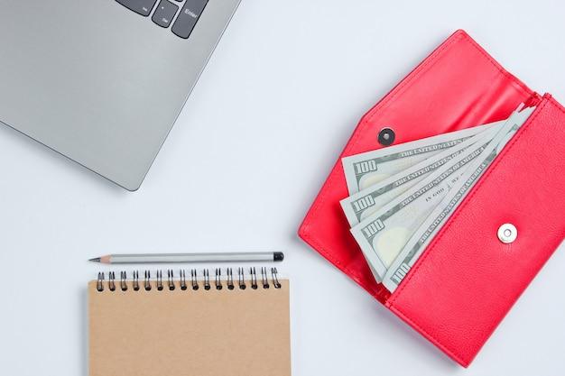 Banconote in un portafoglio e un laptop