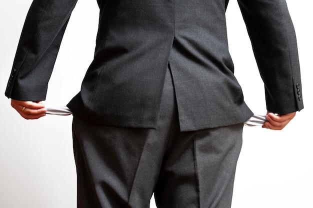 Uomo d'affari in bancarotta che mostra le tasche vuote dei pantaloni