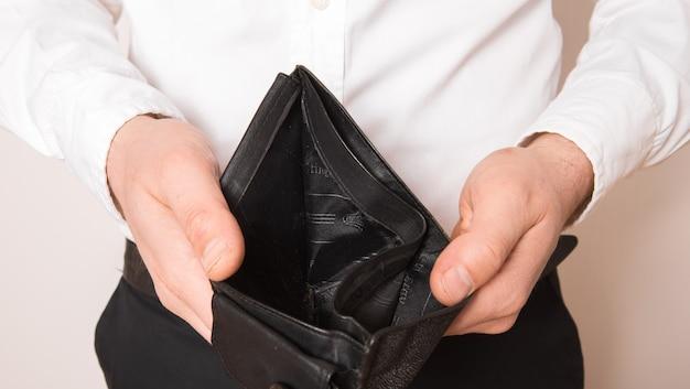 Fallimento - imprenditore in possesso di un portafoglio vuoto. uomo che mostra l'incoerenza e la mancanza di denaro e non è in grado di pagare il prestito e il mutuo.