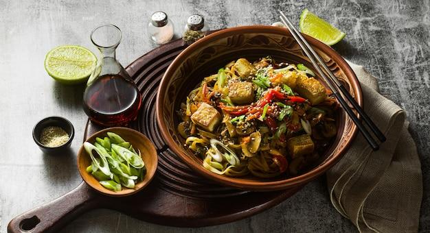 Banner di vegano asiatico soffriggere con tofu, spaghetti di riso e verdure, vista dall'alto.