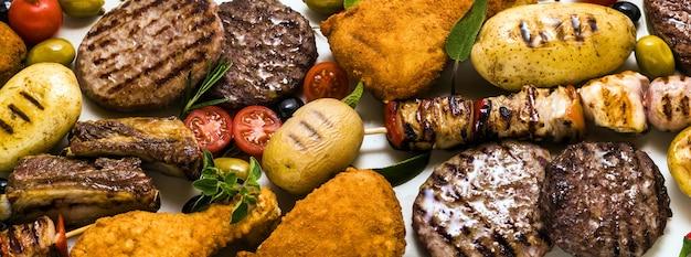 Banner di carne alla brace con diversi tipi di carne: hamburger di manzo, costolette di maiale, polpette di tacchino, cosce di pollo impanate con patate e pomodori, spezie ed erbe aromatiche.