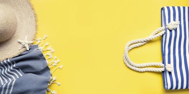 Banner di borsa da spiaggia cappello di paglia asciugamano da spiaggia su sfondo giallo vacanze estive vista dall'alto