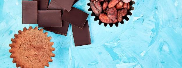 Banner di sfondo di fave di cacao sul tavolo blu. pezzi di cioccolato fondente