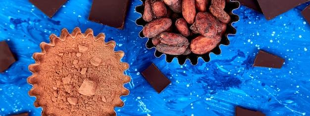 Banner di sfondo di fave di cacao sul tavolo blu.