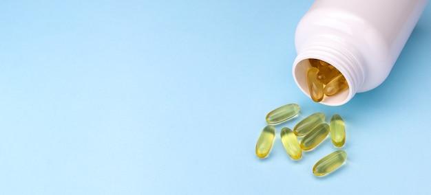 Banner di capsule di gel di olio di pesce capsule di olio di pesce omega 3 fuori contenitore aperto su sfondo blu con...
