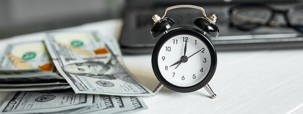 Banner luogo di lavoro moderno di laptop, orologio, denaro, banconote in dollari