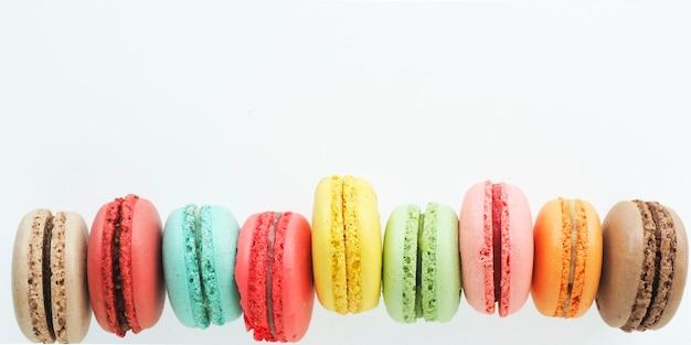 Banner di macarons multicolori su sfondo bianco. copia spazio.