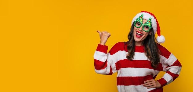 Foto banner di una bella donna moderna eccitata con divertenti occhiali di natale e cappello di babbo natale si sta divertendo mentre posa contro un muro giallo