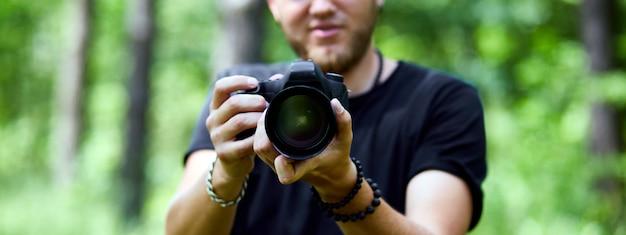 Banner di ritratto di un fotografo maschio che copre il viso con la fotocamera all'aperto per scattare foto, giornata mondiale del fotografo, giovane con una fotocamera in mano.