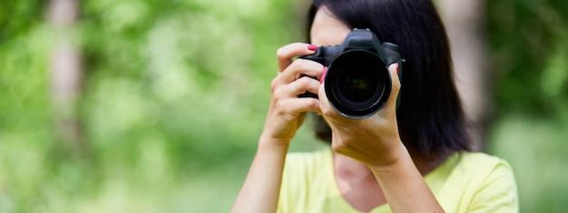 Banner di ritratto di una fotografa donna che copre il viso con la fotocamera all'aperto per scattare foto, giornata mondiale del fotografo, giovane donna con una fotocamera in mano.