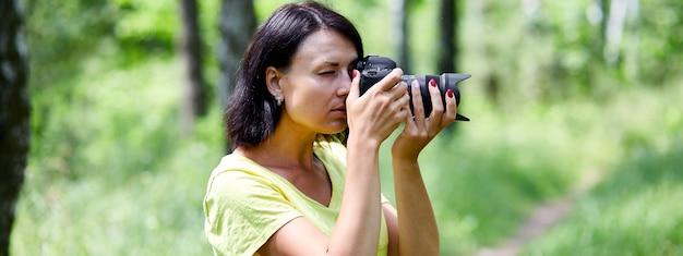 Banner di ritratto di una donna fotografa che si copre il viso con la macchina fotografica