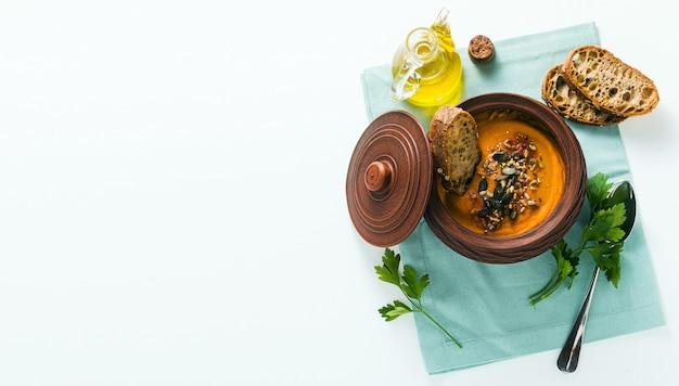 Banner di zuppa di zucca con semi e pane di segale fresco in una ciotola di argilla sul tavolo
