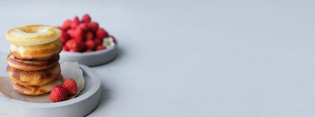 Bandiera. ciambella al forno rotonda con fragole su uno sfondo di cemento grigio. minimalismo.