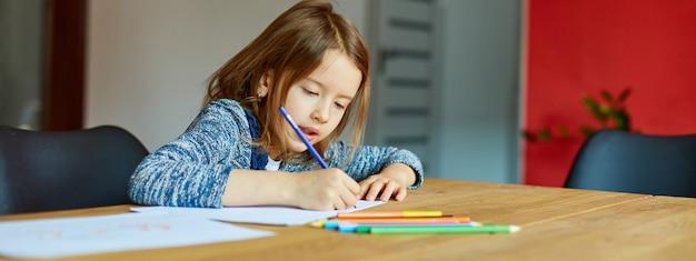 Striscione della ragazza della scuola che disegna e scrive un'immagine con i pastelli, usando matite colorate a tavola a casa, disegno del bambino.