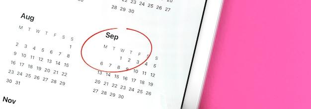 Banner mese scolastico di settembre cerchiato in rosso, calendario, segnato il primo piano del mese, sfondo rosa con foto dello spazio della copia