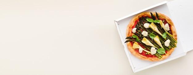 Banner di asparagi pizza vegana in una scatola per la consegna, pubblicità o menu