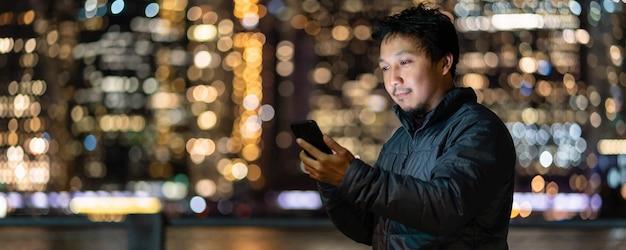 Banner e pagina web o modello di copertina di un uomo asiatico che utilizza un telefono cellulare intelligente