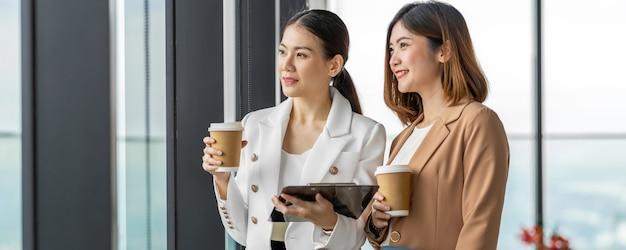 Un'insegna, una pagina web o un modello di copertura di due donne di affari asiatiche che parlano durante la pausa caffè in ufficio moderno