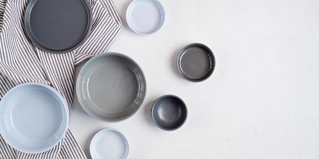Banner con piatti in ceramica su sfondo grigio chiaro di cemento