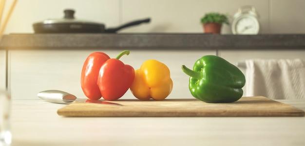 Banner con tagliere con peperoni dolci rossi, gialli e verdi su uno sfondo di cucina moderna. ingrediente vegetale, cucinare cibo sano concetto foto