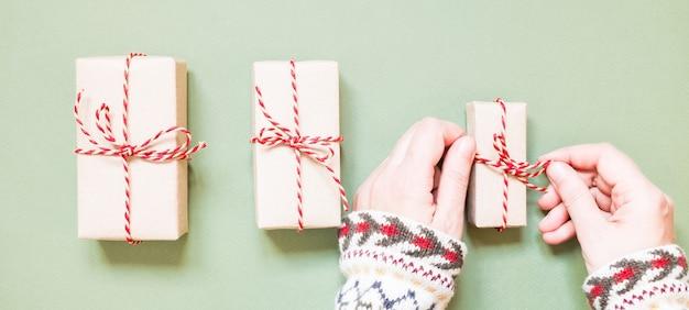 Banner con mani femminili che legano un fiocco su un regalo di natale