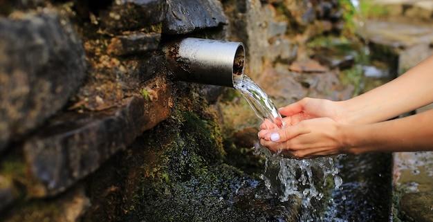 Banner of woman raccoglie acqua pura nel palmo della mano dalla sorgente nel muro, tienila e bevila