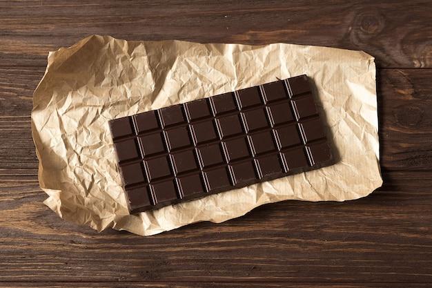Barra di cioccolato fondente nero su fondo di legno marrone, vista dall'alto