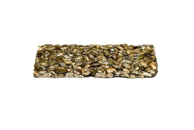 Bar con noci isolate su uno sfondo bianco. barretta ai semi di zucca. vista dall'alto.