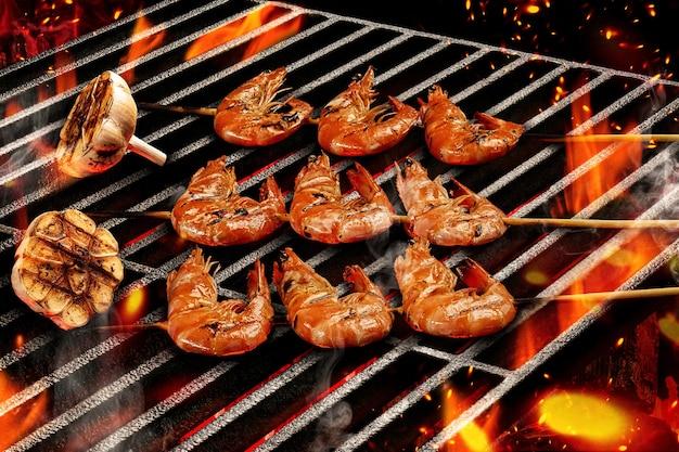 Barbecue barbecue deliziosi gamberi arrostiti alla griglia su spiedini di legno con metà di aglio fuoco fiammeggiante ...