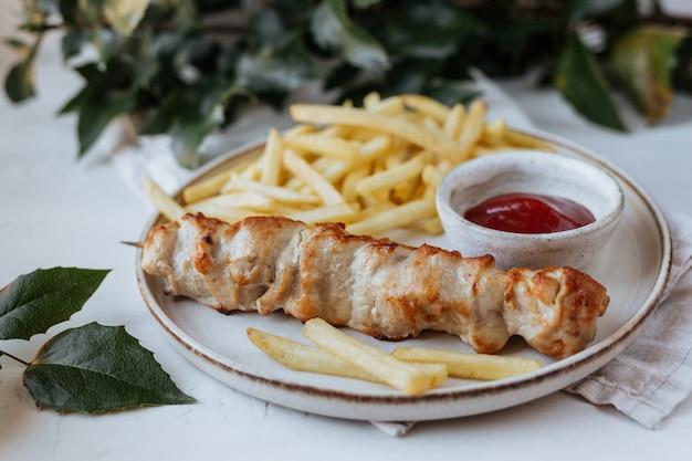Su un piatto venivano serviti pollo alla griglia, patatine fritte e salsa di pomodoro