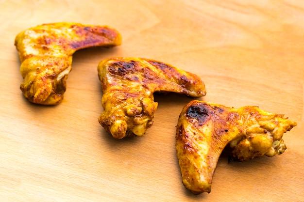 Le ali di pollo barbecue si chiudono su vassoio in legno girato con messa a fuoco selettiva.