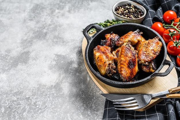 Barbecue di ali di pollo in salsa di miele. carne di pollame al barbecue. sfondo grigio. vista dall'alto. copia spazio.