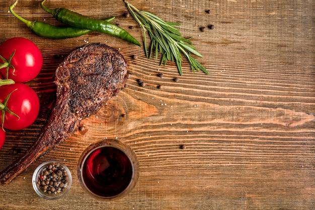 Barbecue invecchiato secco nervatura di manzo con verdure e bicchiere di vino rosso close-up su sfondo di legno. vista dall'alto. copia spazio. natura morta. lay piatto