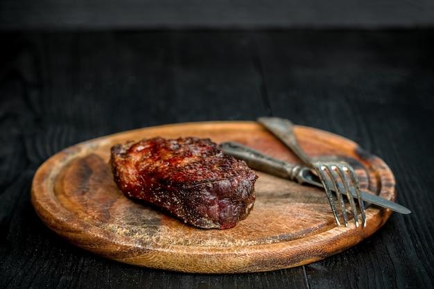 Barbecue dry invecchiato ribeye steak con coltello e forchetta sul tagliere. fondo in legno nero. natura morta. copia spazio. avvicinamento