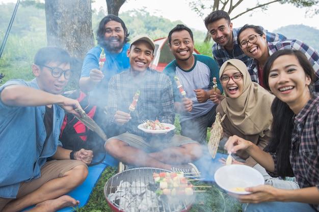 Barbecue nella foresta mentre il campeggio insieme