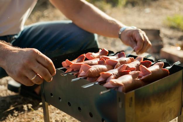 Salsicce fritte alla griglia su spiedini su un barbecue