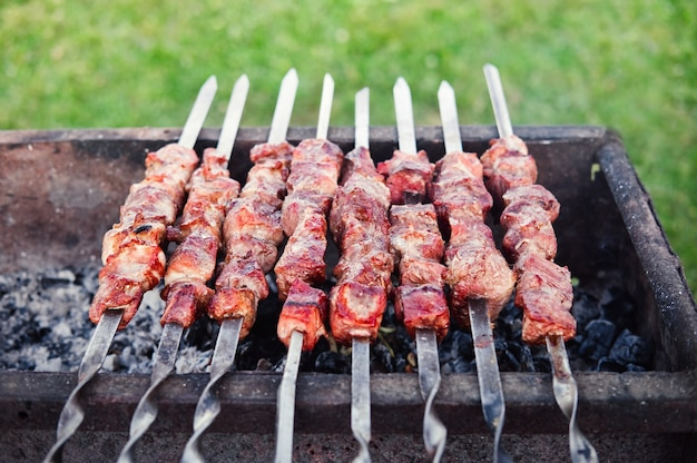 Barbecue alla griglia. kebab su spiedini che cucinano all'aperto. cuocere gli shashlik su spiedini all'aria aperta. Foto Premium