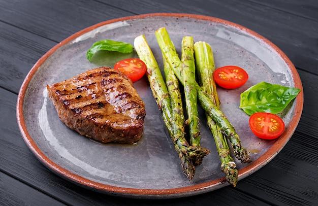 Barbecue bistecca di manzo alla griglia con asparagi e pomodoro
