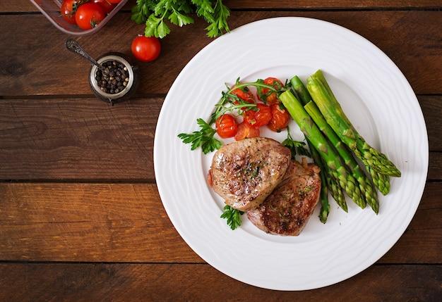 Barbecue di carne di manzo alla griglia con asparagi e pomodori.