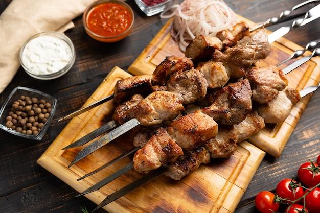 Barbecue di carne di maiale alla griglia shashlik spiedini di carne su spiedino di metallo su tagliere in stile rustico