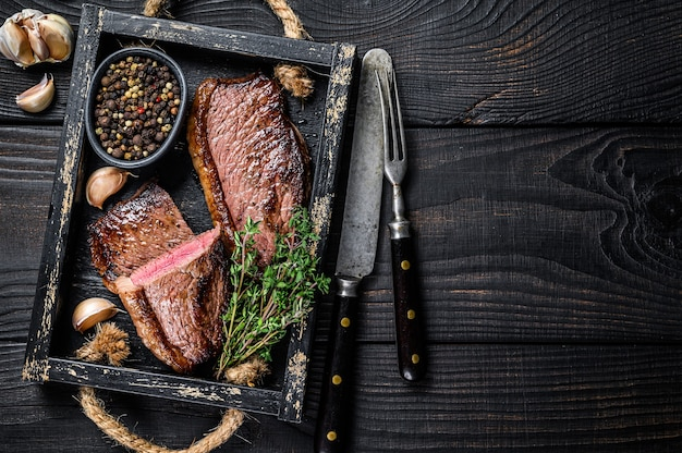 Tappo di groppa alla griglia barbecue o bistecca di carne di manzo picanha brasiliana in un vassoio di legno. fondo in legno nero. vista dall'alto. copia spazio.