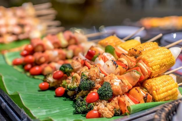 Maiale a cubetti magro al barbecue con verdure di mais e griglia di pomodoro messa a fuoco selettivasano delizioso