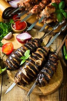 Menu barbecue melanzane alla griglia con pancetta salsicce alla griglia e spiedini di carne alla griglia