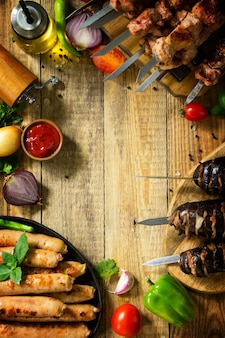 Menu barbecue spiedini di carne alla griglia salsicce alla griglia e melanzane alla griglia con pancetta vista dall'alto