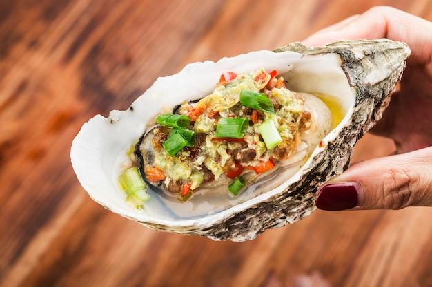 Ostrica aperta fresca cotta al barbecue con aglio,