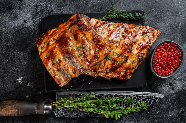 Costine di maiale alla griglia su una tavola di marmo