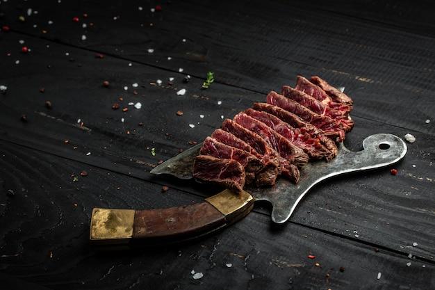 Barbecue rib eye steak bistecca di scamone wagyu invecchiato a secco su coltello da macellaio di carne. banner, posto ricetta menu per testo, vista dall'alto.
