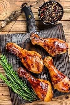 Barbecue cosce di pollo arrosto su un tagliere di legno.